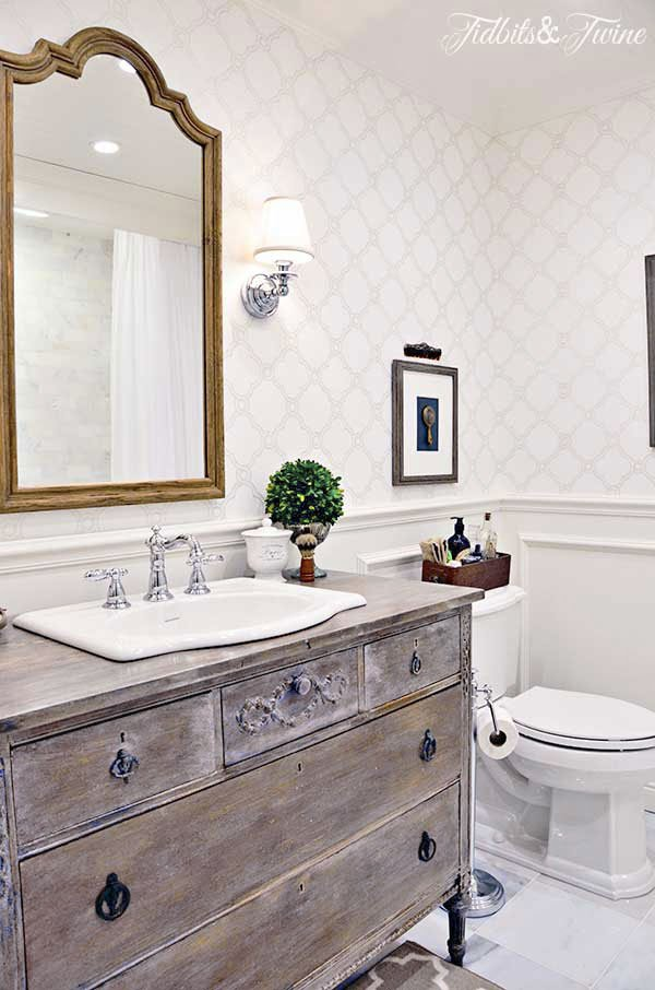 bathroom with dresser as a vanity wainscotting and wallpaper