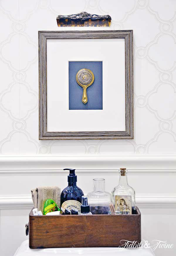 Framed silver mirror and comb hanging on wall above toilet with sewing drawer holding essentials