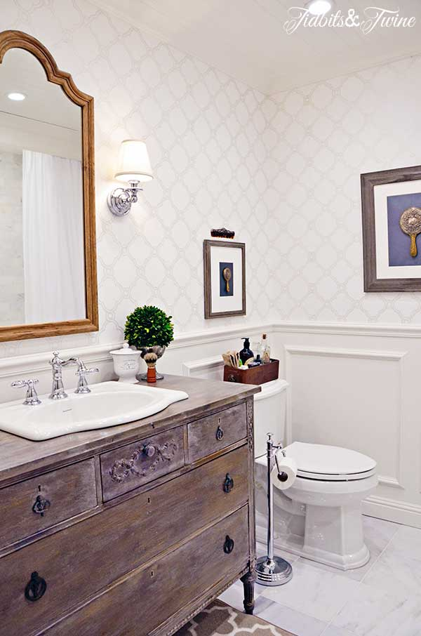 A guest bathroom transformation: from builder-grade to beautiful! Beadboard ceiling, wallpaper, sconces, marble floors, and a vanity converted from a vintage dresser!