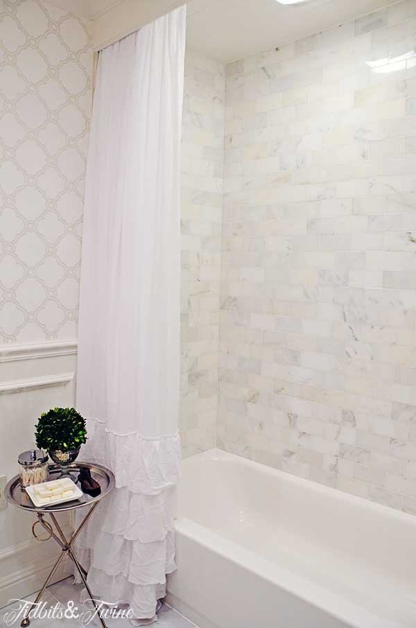 TIDBITS&TWINE Guest Bathroom Remodel - Marble tile tub with ruffle shower curtain