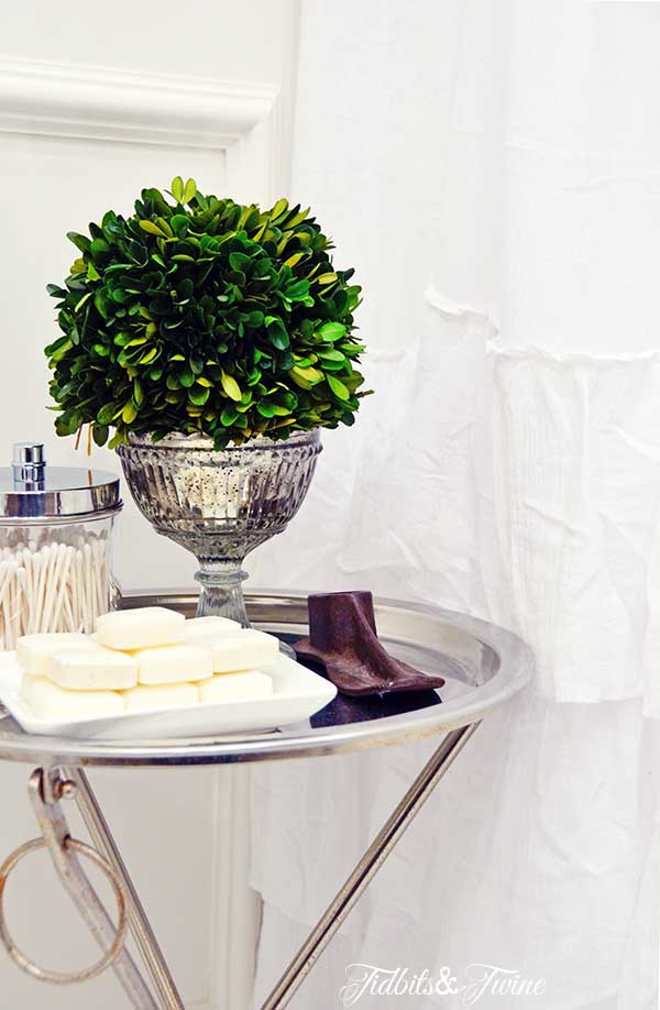 Closeup of silver butler tray in bathroom with small soaps and Q-tips on top and preserved boxwood ball
