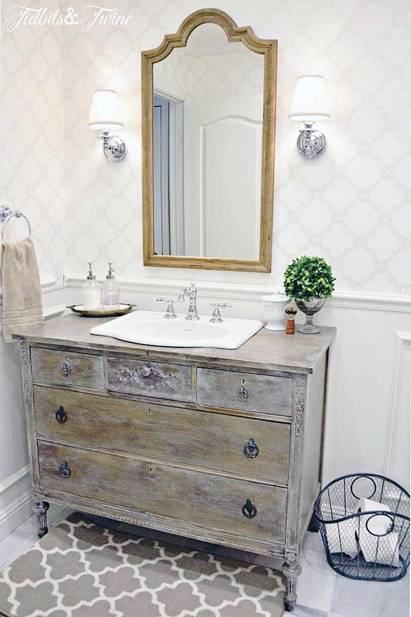 sconces with shades flank a wooden mirror in bathroom with dresser vanity wallpaper wainscotting and beadboard ceiling