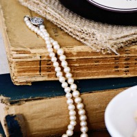 closeup of vintage books with white pearl necklace draped across them