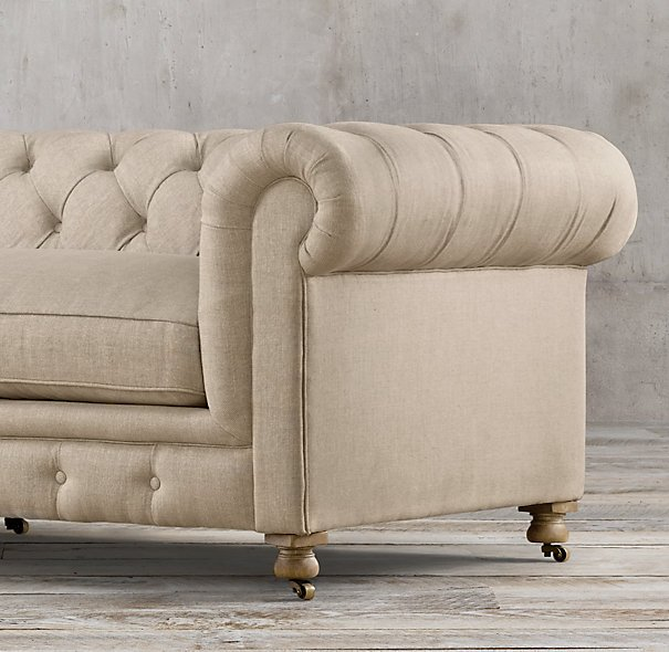 {A button-tufted sofa with the fabric tucked - not stitched - into the tufting to create a diamond pattern}