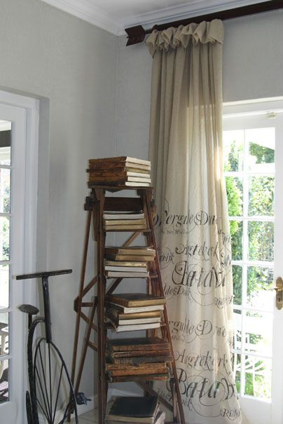 rustic ladder in an empty living room corner stacked with antique books and drapery with antique writing on it