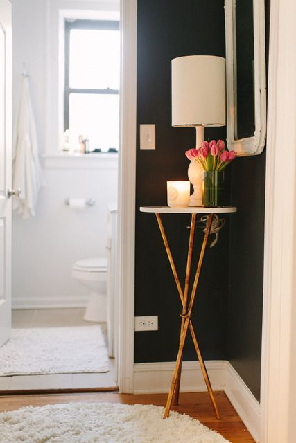 small gold three legged side table filling the corner of a room topped with a lampa nd flowers