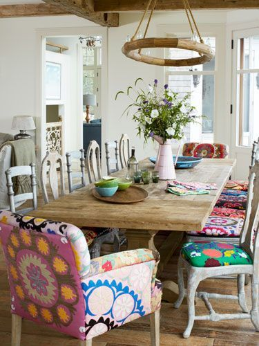Dining room with trestle table and mixed french dining chairs with bold prints