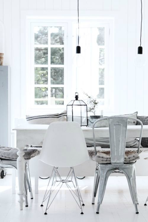 White contemporary dining room with mismatched chairs and white farmhouse table