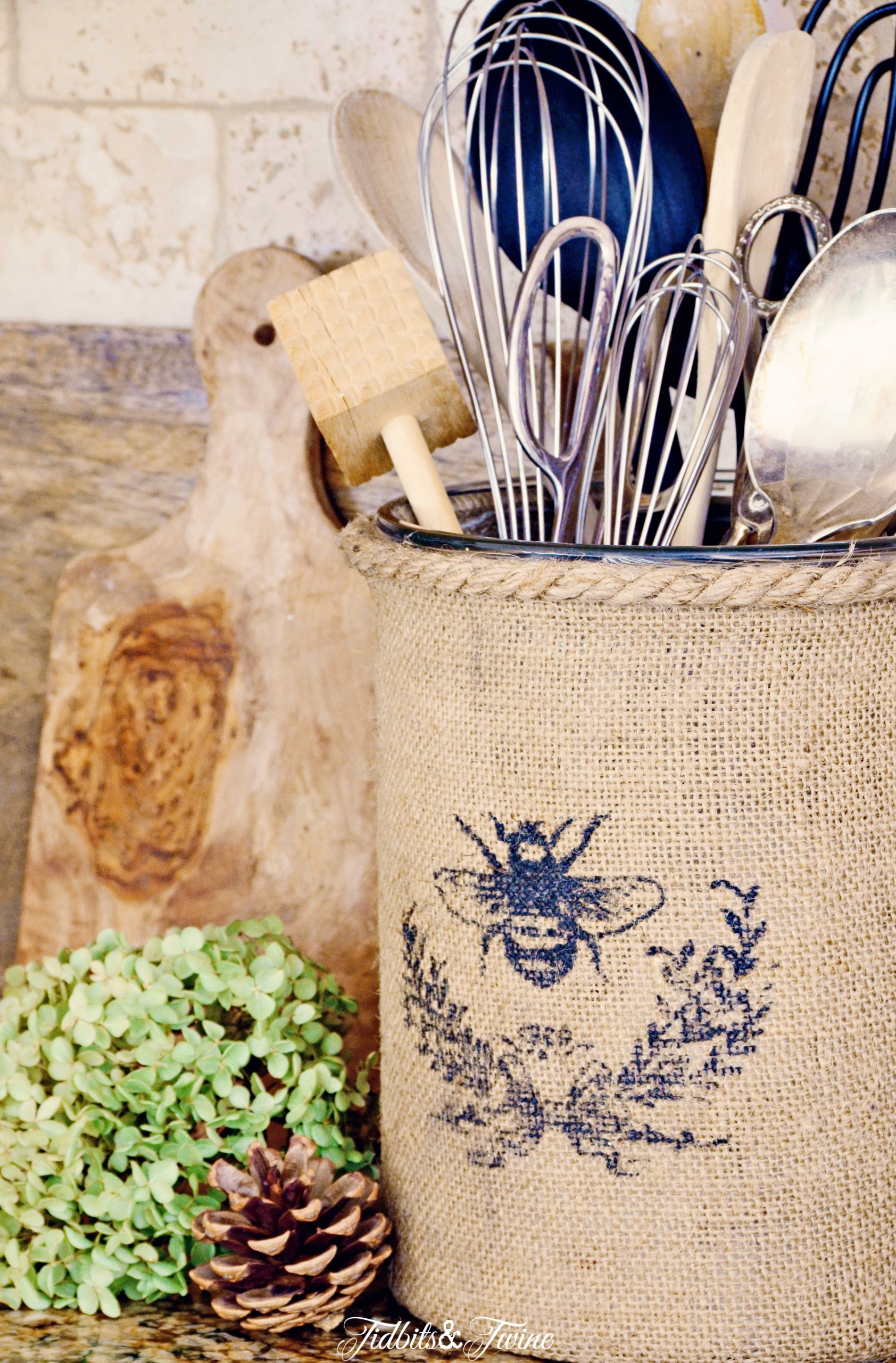 Burlap covered vase holding kitchen utensils in a French farmhouse kitchen