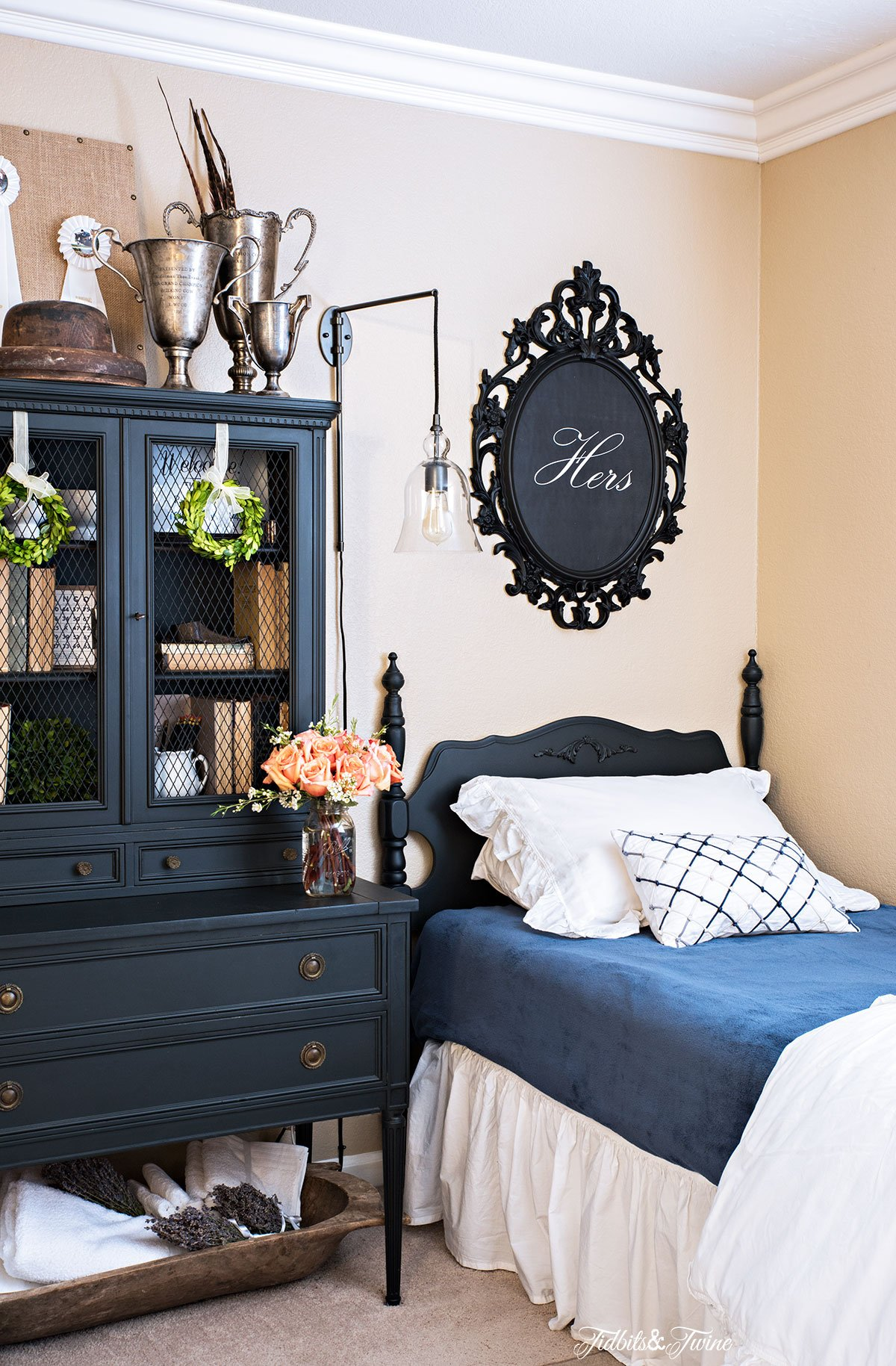 black antique bed with blue and white bedding and black artwork above and black antique hutch with books and trophies