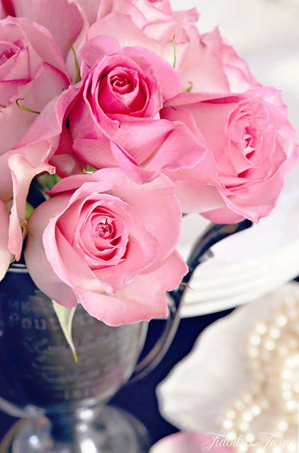 closeup of pink roses in an antique trophy cup with string of pearls on the background