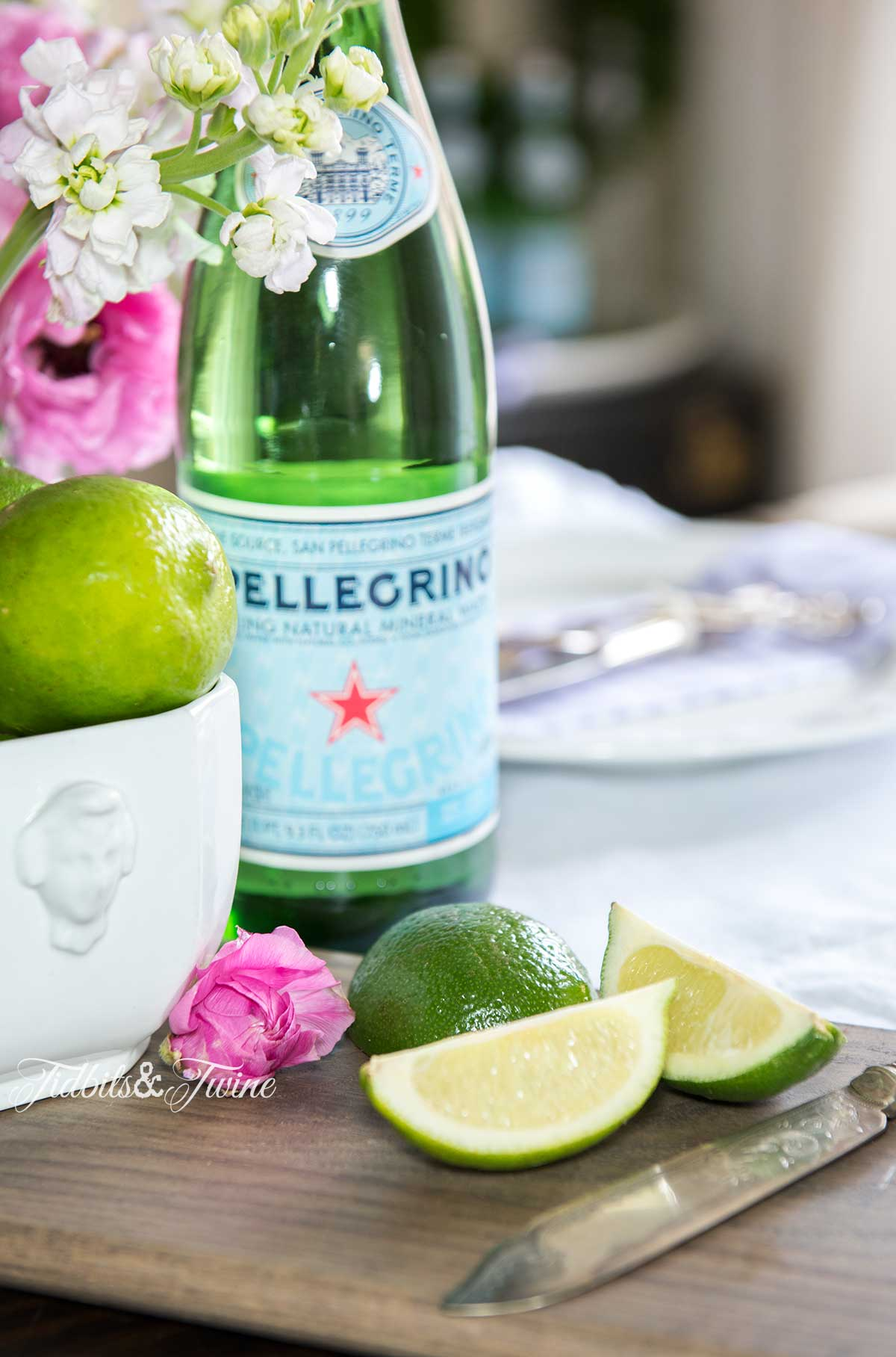 closeup of cut limes on board next to ironstone bowl of limes with pellagrino and pink flowers