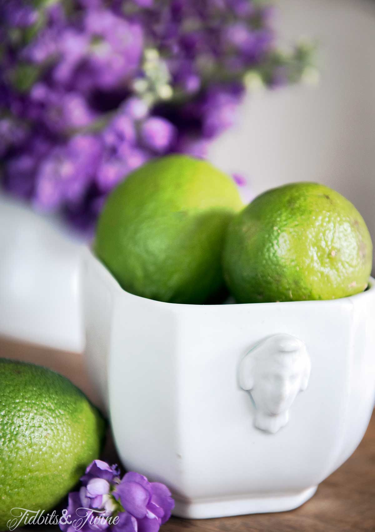 Limes in an ironstone pot with purple flowers for dining room centerpiece