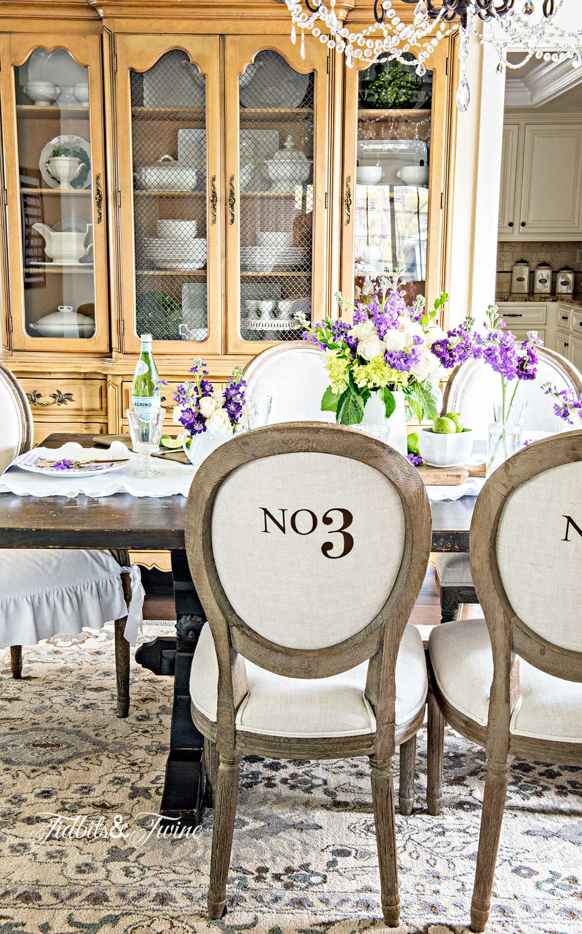 spring tablescape in french dining room with numbered chairs and crystal chandelier