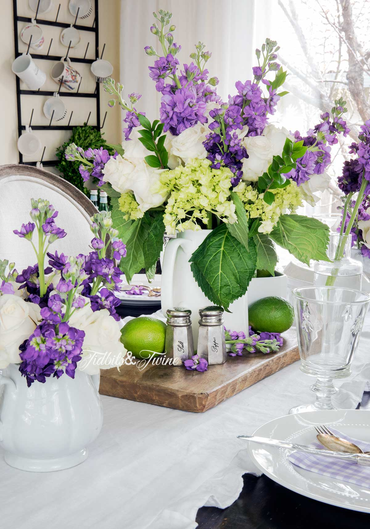 Purple white and green flower centerpiece on a bread board with limes