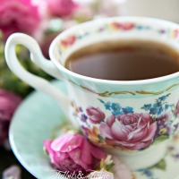 turquoise and pink antique teacup filled with coffee with pink flowers in the saucer and pink flowers in background