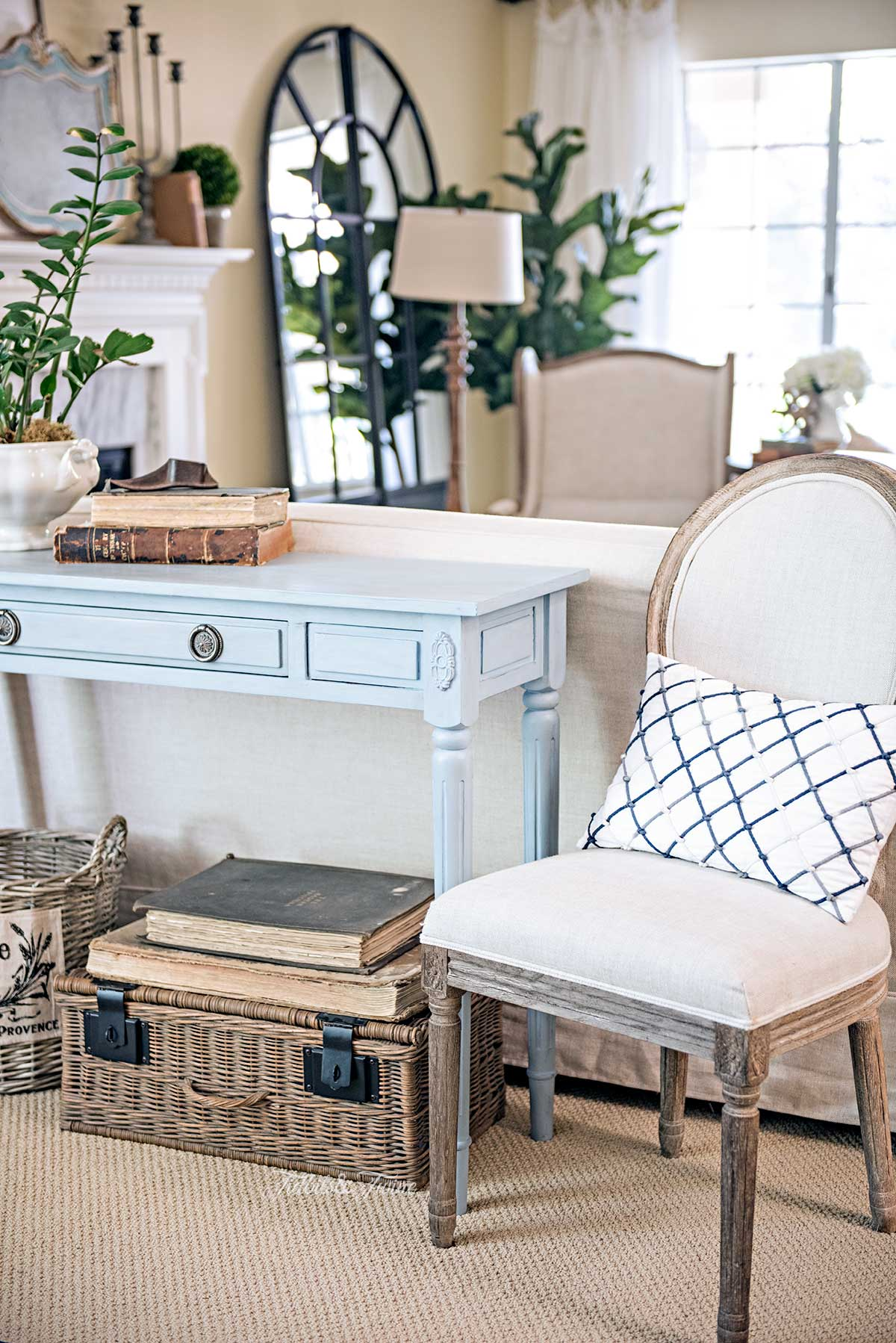 A French living room with a blue console table behind a sofa with a book and plant vignette