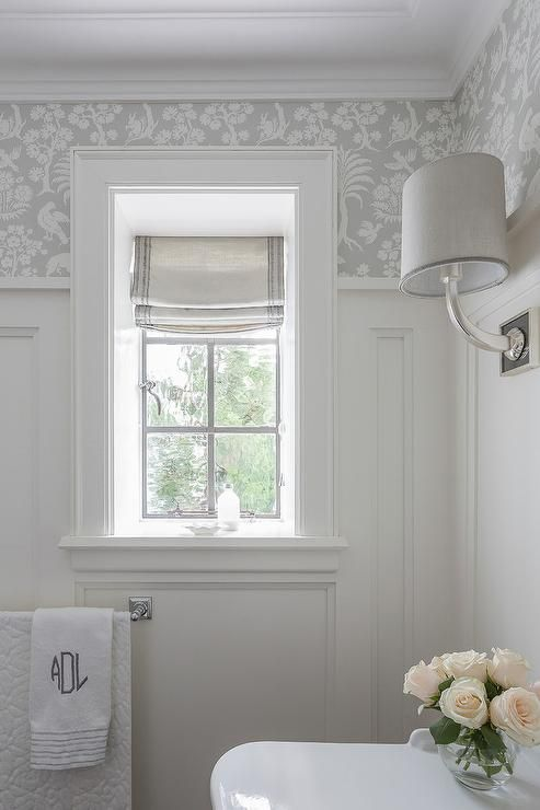 small bathroom with white trim on bottom and gray floral wallpaper on top