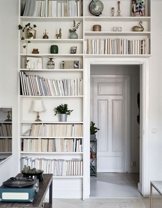 White built in shelves filled with books that surround a doorway