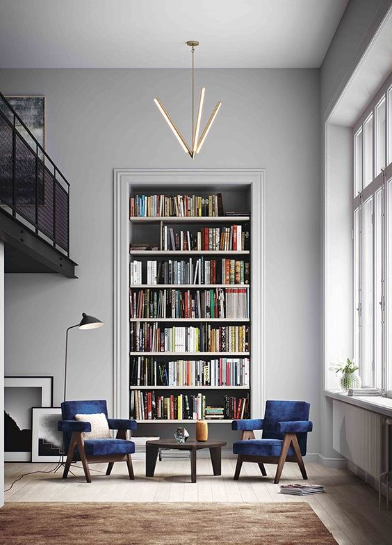 Tall recessed bookcase filled with books in a gray living room with blue chairs