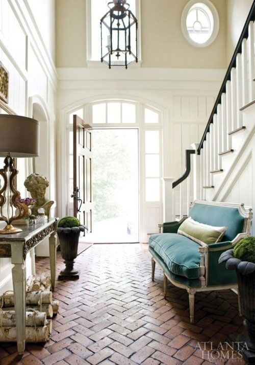 Two story foyer with herringbone brick floor and blue velvet settee
