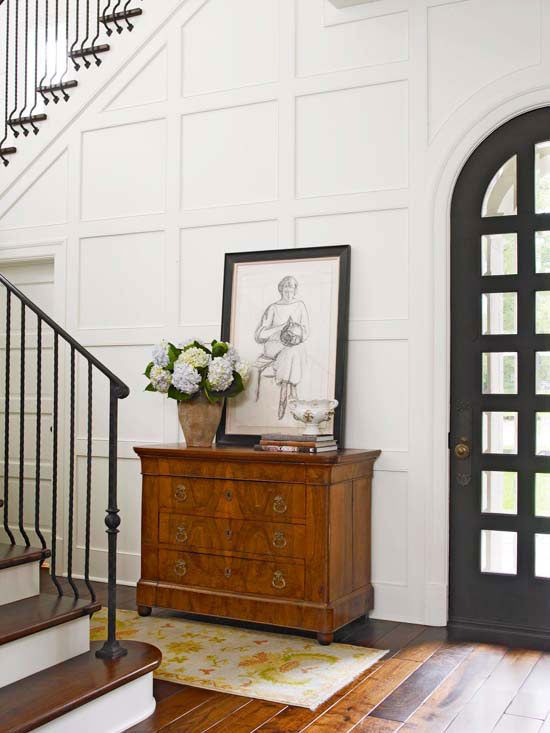 White board and batten wall trim in an entryway with a small decorative dresser and artwork