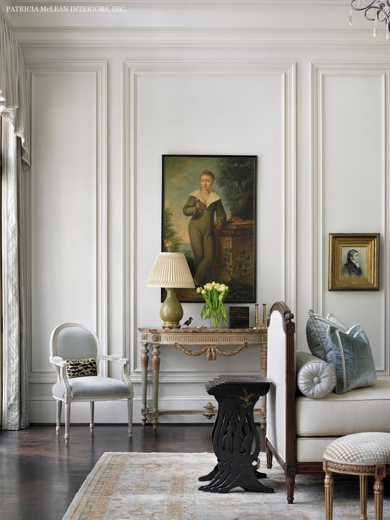 White wall trim on living room walls with vintage artwork a french chair and a settee