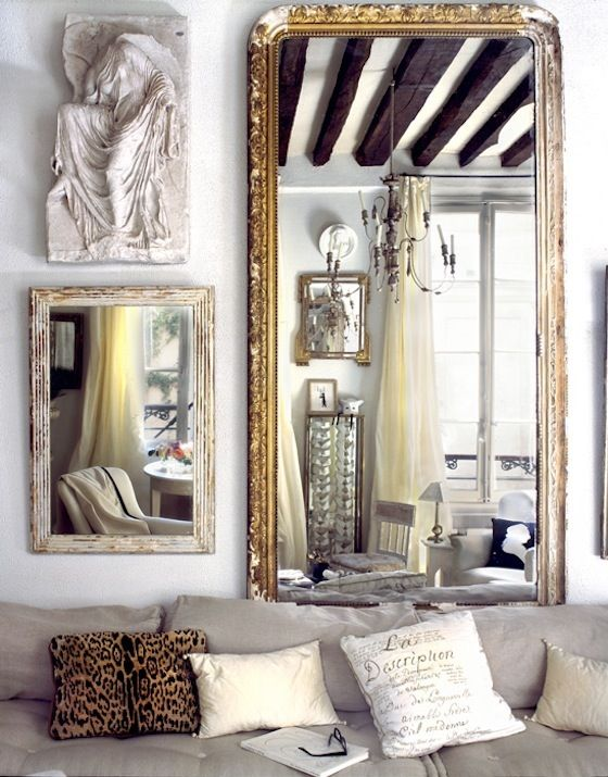 Tall gold antique mirror above a sofa with a small mirror and sculpture next to it on the wall
