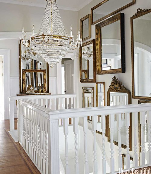 Grouping of gold antique mirrors hanging above stairs with a crystal chandelier