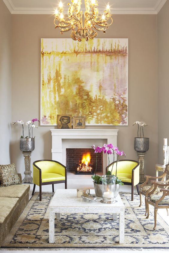 Pink and yellow oversized art canvas above a white fireplace with two yellow chairs in front