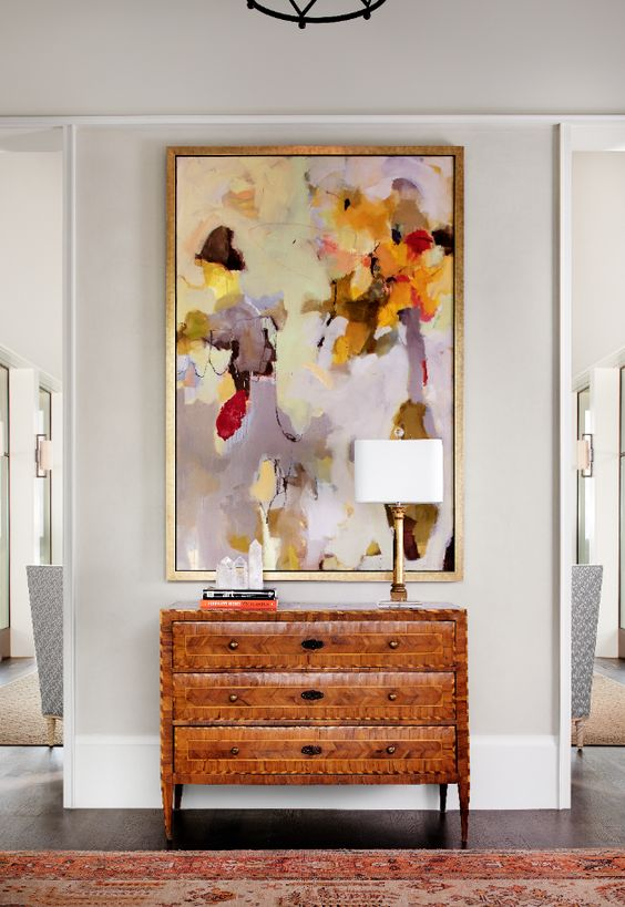Oversized abstract yellow red and lavender artwork above a set of drawers in foyer
