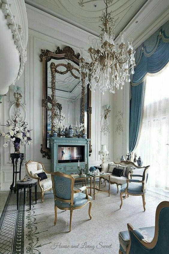 White an blue french elegant living room with gold mirrors crystal chandelier and blue curtains