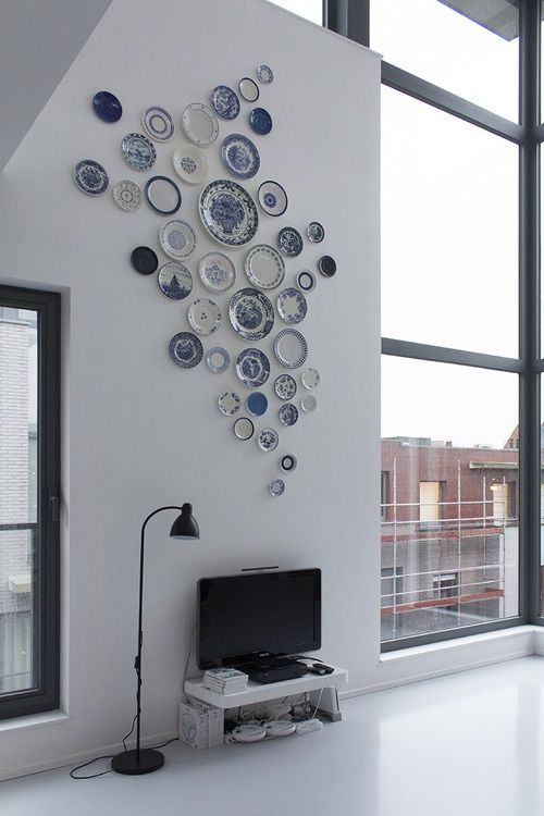 blue and white plates hanging on the wall of a modern loft above a tv