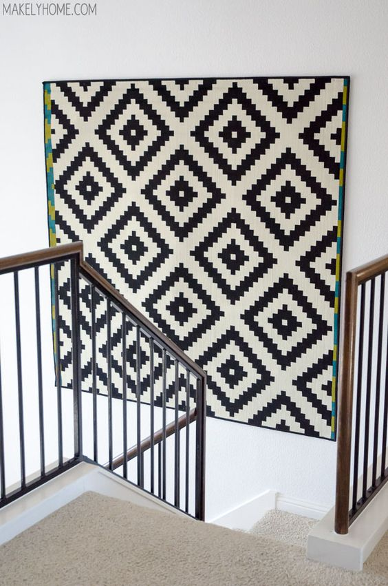 Black and white geometric wall hanging on the stairwell with white walls
