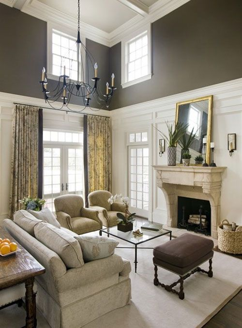 Vaulted living room with white trim on bottom and brown walls on top