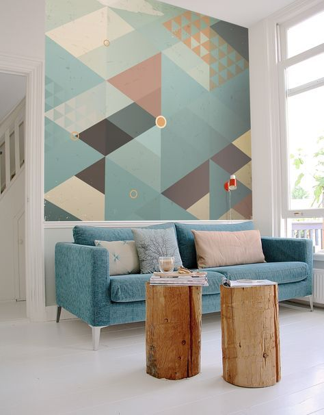Blue and gray triangle geometric mural above a blue sofa with wood stump coffee table