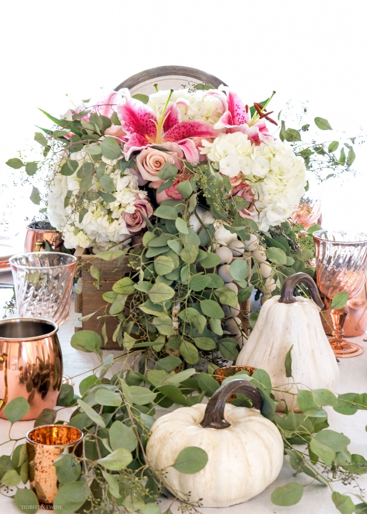 Fall dining table with wooden box overflowing with eucalyptus hydrangeas and white pumpkins