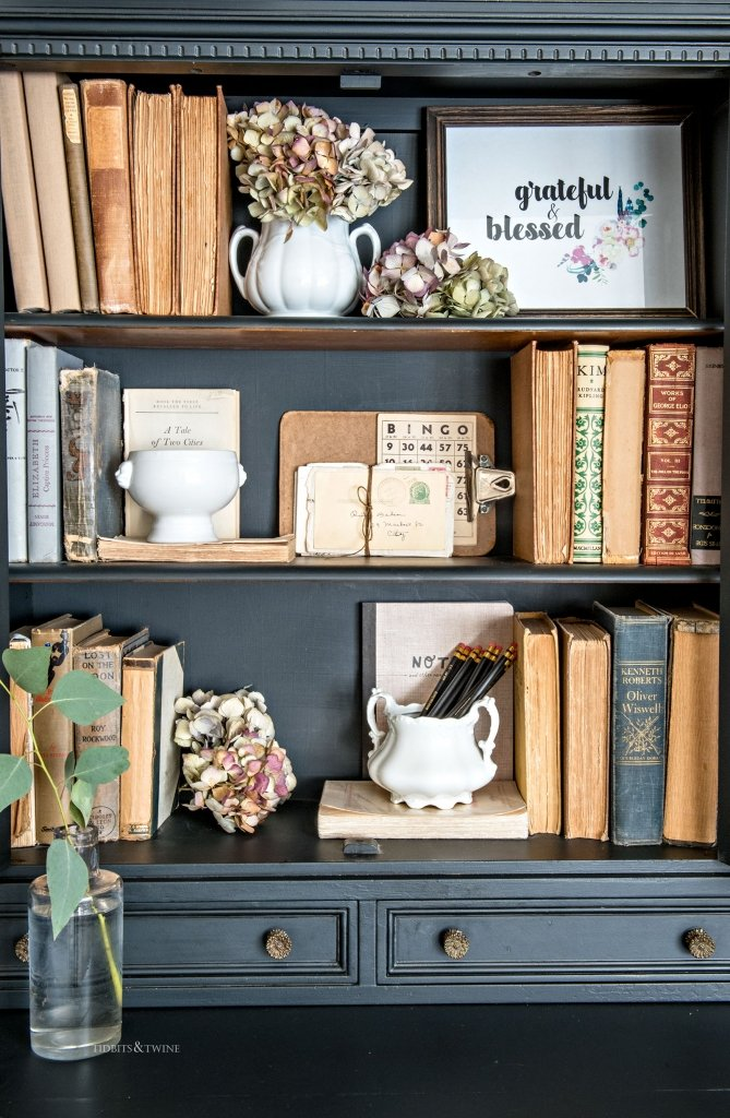 Black styled bookshelf holding vintage books and dried flowers for Fall