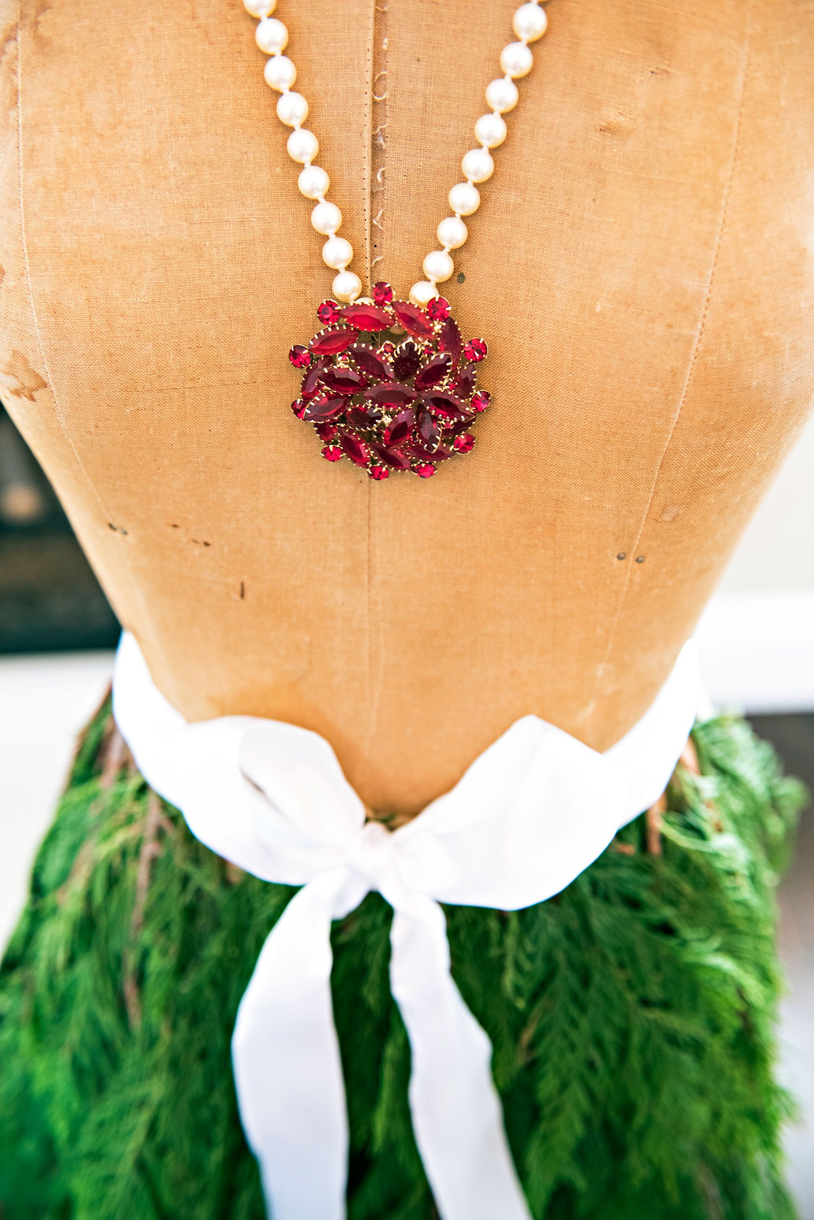 Vintage dress form with red broach and pearl necklace and cedar skirt tied with a white bow