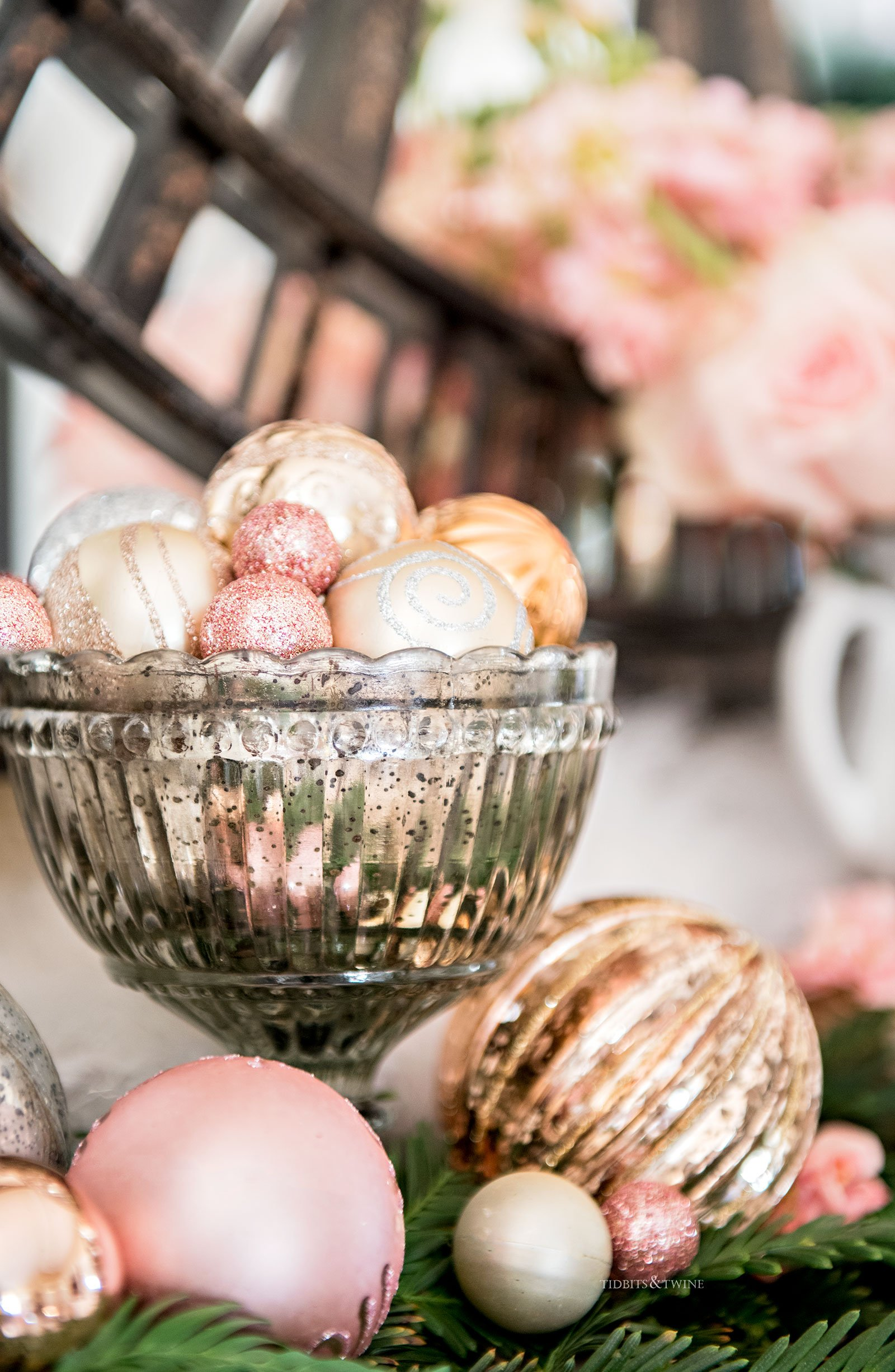 Silver mercury compote filled with pink ornaments sitting on top of cedar branches