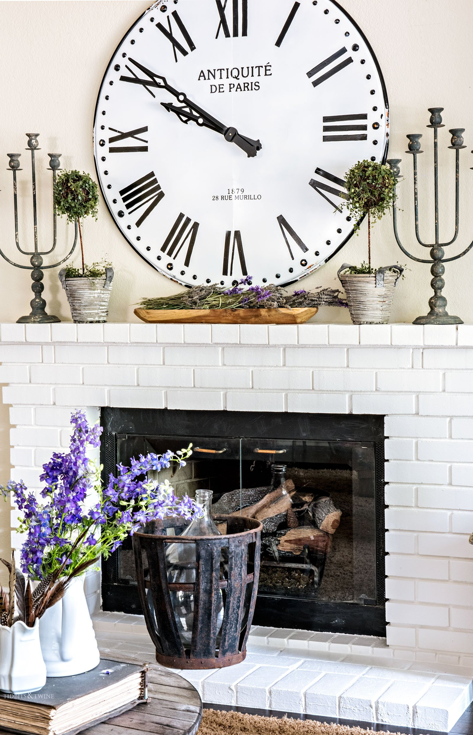 Oversized clock above a white brick fireplace with candlesticks and antique demijohn