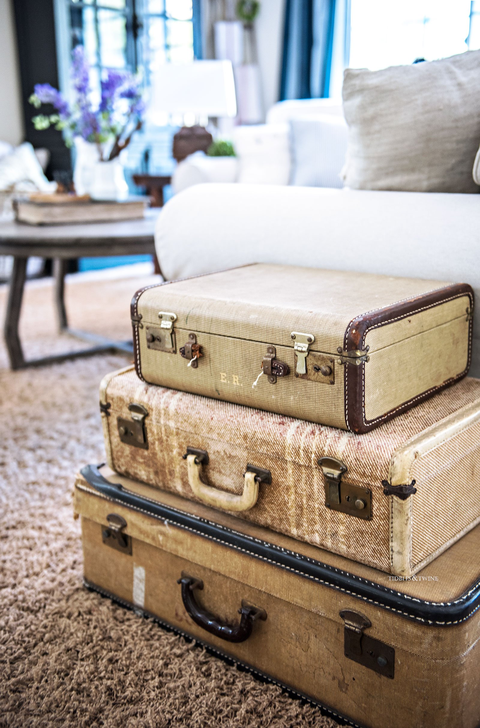 Stacked vintage suitcases used as a side table in a family room