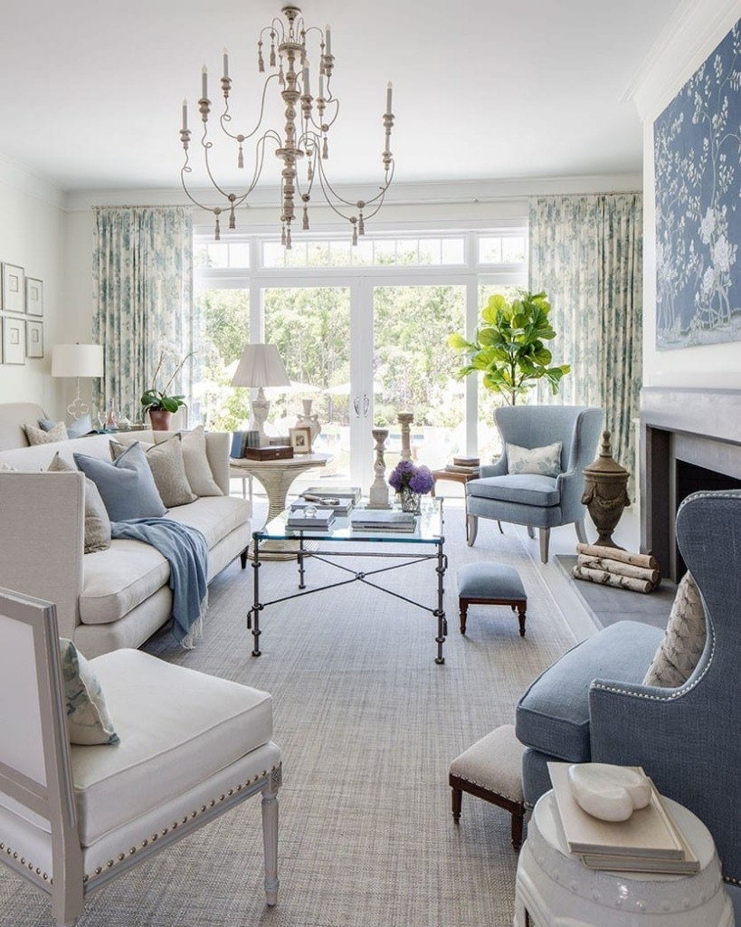Traditional living room with white sofa and blue chairs around fireplace
