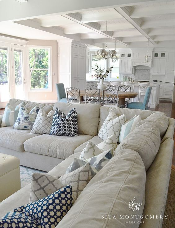 Large beige sectional in great room with white kitchen and blue accents