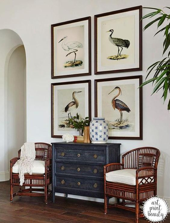 Entryway with bird pictures hanging above antique chest of drawers and chairs