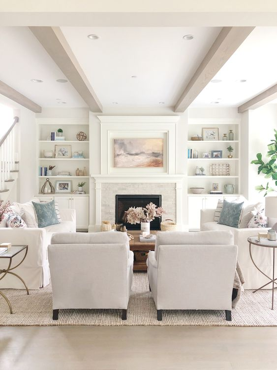 White family room with two chairs and two slipcovered sofas.