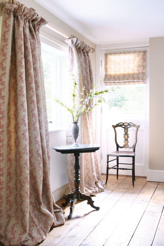 Floral curtains that puddle on the floor with a single chair and side table