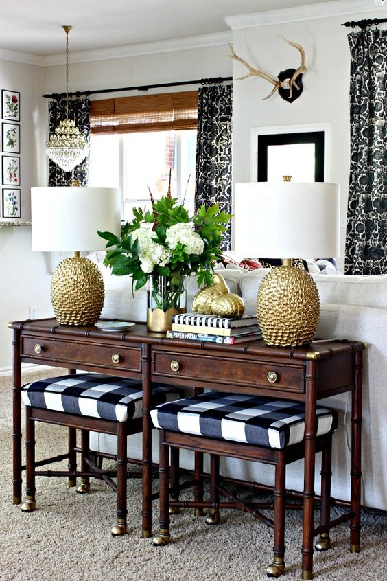 Dark wood sofa table with gold lamps on top and plaid stools tucked underneath