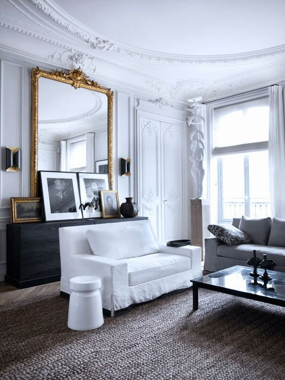 white french living room with large gold mirror and artwork leaning in front