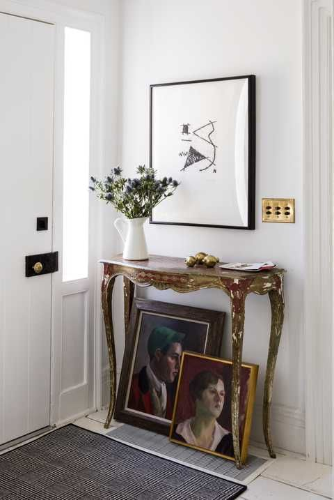 white entry with french console table and framed art leaning on the floor